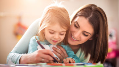 childcarer and girl drawing