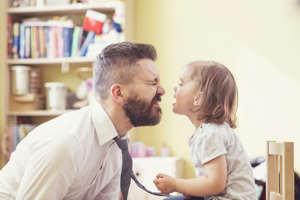man and daughter making faces