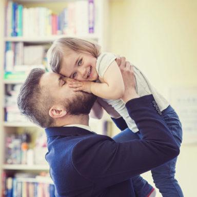 man in suit lifting daughter