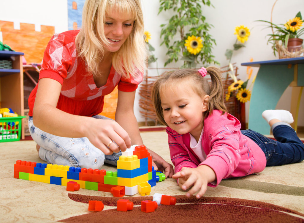 woman and girl with building blocks