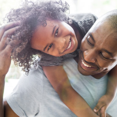 A photo of happy girl with arms around father. Young man is looking at daughter smiling. They are in casuals at home.